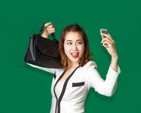 Lady show off her new purse by mobile phone. Asian teen selfy cell phone with new handback leather to show materialism in generation Stock Image