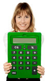 Lady showing big green calculator. Smiling woman showing big green calculator Royalty Free Stock Image