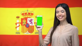 Lady showing cellphone with green screen, Spanish flag on background, travel app. Stock footage stock video