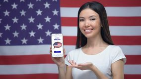Lady showing cellphone with learn English app, USA flag on background, education. Stock footage stock video footage