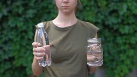 Lady showing glass mug to camera, preferring it to plastic bottle, saving earth