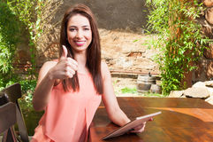 Lady showing thumb up on terrace holding tablet Royalty Free Stock Images