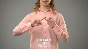 Lady signing you are my friend in asl, text on background communication for deaf. Stock footage stock video footage