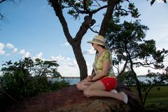 Lady Siiting on a Big Rock. Lady Sitting on a Big Rock Wearing a Hat and Shorts Enjoying the Great Outdoors Royalty Free Stock Images