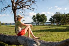 Lady Siiting on a Fallen Tree. Lady Sitting on a Fallen Tree Wearing a Hat and Shorts Enjoying the Great Outdoors Stock Images