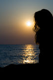 Lady silhouette at sunset. On the sea Royalty Free Stock Images