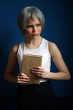 Lady in silver wig posing with book. Close up. Blue background. Lady in silver wig posing with book, silver wig, cosplay, high fashion look, perfect make-up Royalty Free Stock Images