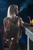 Lady sitting alone in the night club and smoking cigarette Stock Photos