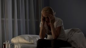 Lady sitting on bed, unable to fall asleep due to severe migraine and bad pain stock photography