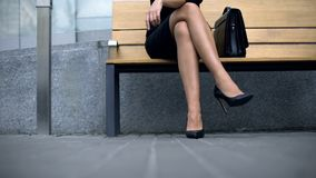 Lady sitting on bench, waiting for client, tired of wearing high-heeled shoes stock images