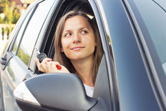 Lady sitting in a car and showing key Stock Images