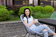 Lady sitting in chair at cafe near green plants and drinking coffee. Smiling woman sitting in chair at cafe near green plants and drinking coffee. Concept of Stock Photography