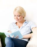 Lady sitting on the couch reads a book Stock Photos
