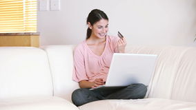 Lady sitting on the couch while using her credit card stock footage
