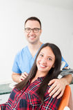 Lady sitting in dentist chair with doctor aside Royalty Free Stock Images