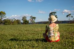 Lady Sitting on the Grass Relaxing. Lady Sitting on the Grass Wearing a Hat and Shorts Enjoying the Great Outdoors Stock Photos