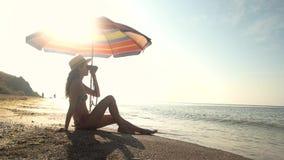 Lady sitting near beach umbrella. stock footage