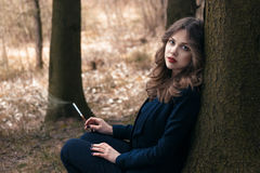 Lady sitting near the tree. Young lady sitting near the tree and smoking Stock Photography