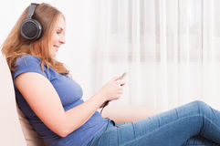 Free Lady Sitting On Couch Listening To Headphones Holding Smartphone Royalty Free Stock Image - 81645106
