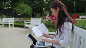 Lady Sitting in the Park, Using Laptop. Data Entry. Beautiful brunnette lady sitting on a white bench in the park and using a laptop. Data entry. Medium shot Royalty Free Stock Image