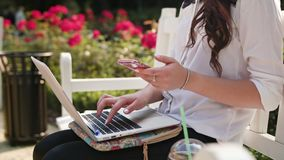 Lady Sitting in the Park and Using Laptop and Phone. Beautiful brunnette lady sitting on a white bench in the park and using a laptop and a telephone. Close-up Stock Images