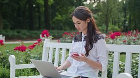 Lady Sitting in the Park and Using Laptop and Phone. Beautiful brunnette lady sitting on a white bench in the park and using a laptop and a telephone. Medium Stock Photography
