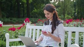 Lady Sitting in the Park and Using Laptop and Phone. Beautiful brunnette lady sitting on a white bench in the park and using a laptop and a telephone. Medium Royalty Free Stock Photos