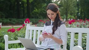 Lady Sitting in the Park and Using Laptop and Phone. Beautiful brunnette lady sitting on a white bench in the park and using a laptop and a telephone. Medium Stock Images