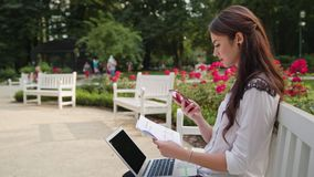 Lady Sitting in the Park and Using Laptop and Phone. Beautiful brunnette lady sitting on a white bench in the park and using a laptop and a telephone. Medium Royalty Free Stock Photo