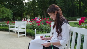 Lady Sitting in the Park and Writing. Beautiful brunnette lady sitting on a white bench in the park and writing. Medium shot stock footage