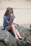 Lady sitting and relaxing on sea rocks Royalty Free Stock Photography