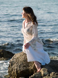 Lady Sitting on Sea Rock. Beautiful young lady sitting on sea stone ethnic dress Royalty Free Stock Photography