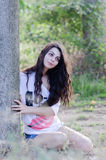 Lady sitting under the tree wearing a white shirt and shorts Stock Photo