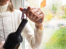 Lady sitting on the windowsill opens a bottle of wine with a corkscrew. royalty free stock photography