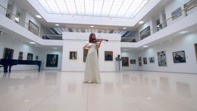 A lady is skillfully playing the violin in the gallery. 4K stock video