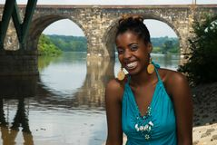 Lady with a smile. African american laughs as she sits by the river stock photos