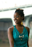 Lady smiles. African american smiles while sitting by bridge stock photography