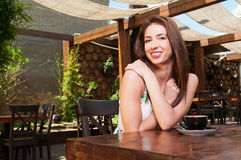 Lady smiling outside on terrace having coffee Royalty Free Stock Photos