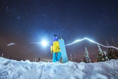 Lady snowboarder night photo against night mountains. Lady snowboarder stands against abstract mountains and stars at night sky Royalty Free Stock Photo