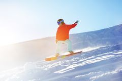 Lady snowboarder at ski slope in sun light stock photography