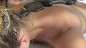 Lady at spa treatment massage. Basalt hot stones with massage oils treatment. HD. Lady at spa treatment massage. Basalt hot stones with massage oils treatment stock footage