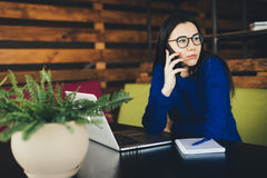 Lady speak on phone at work in modern office. Young lady speak on phone at work in modern office Royalty Free Stock Photos