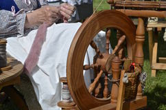 Lady spinning yarn on the wheel Stock Photos
