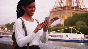Young woman standing on embankment in Paris and watching photos on smartphone