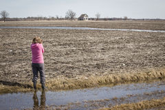 Lady standing in a field photographing an old house in the distance. Stock Photo