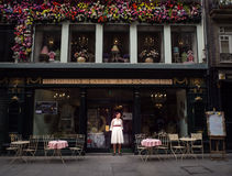 Lady standing in front of antique Porto shop on old street. Shopping district of Porto, Portugal, cafe Royalty Free Stock Photography