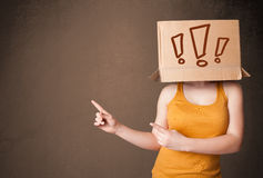 Lady standing and gesturing with a cardboard box on her head with exclamation Stock Images