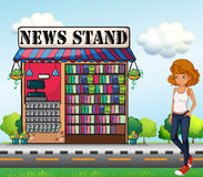 A lady standing beside the news stand Stock Photos