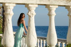 Lady standing on veranda of a beachfront home Royalty Free Stock Images