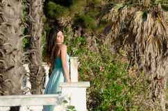 Lady standing on veranda of a beachfront home. Beautiful lady standing on veranda of a beachfront home, wearing a long blue dress, having a great time of her Stock Photo